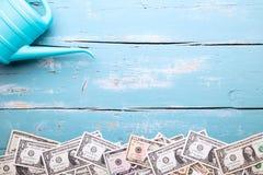 Billets de banque de boîte et de dollar d'arrosage sur le fond bleu, concept GR Photos stock