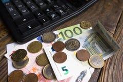 Billets de banque, calculatrice de pièces de monnaie sur la table en bois Photographie stock