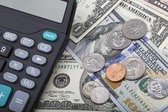 Billets de banque d'USD avec des pièces de monnaie et une calculatrice Image stock