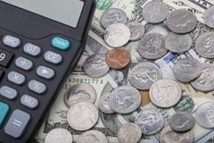 Billets de banque d'USD avec des pièces de monnaie et une calculatrice Images libres de droits