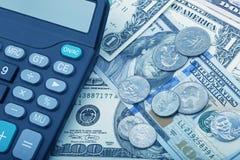 Billets de banque d'USD avec des pièces de monnaie et une calculatrice Photos libres de droits