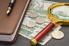 Billets de banque de carnet et pièces de monnaie russes, loupe se trouvant dessus images stock