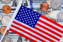 Billets de banque de cent dollars, de beaucoup de pièces de monnaie et de drapeau américain Photographie stock
