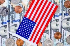 Billets de banque de cent dollars, de beaucoup de pièces de monnaie et de drapeau américain Images libres de droits