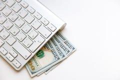 100 billets de banque de dollars US et pièces de monnaie d'argent avec l'ordinateur keyboar Photos stock