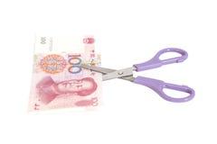 100 billets de banque de yuans avec des ciseaux (devise chinoise) Photographie stock