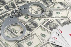 Billets de banque des dollars, menottes, as quatre de jouer des cartes Images stock