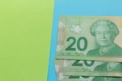Billets de banque de devise canadienne : Dollar Factures sur la table lumineuse colorée image stock