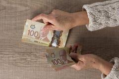 Billets de banque de devise canadienne : Dollar Frais g?n?raux de personne sup?rieure tenant des factures photographie stock