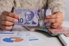 Billets de banque de devise canadienne : Dollar Personne manipulant le papernot photographie stock libre de droits