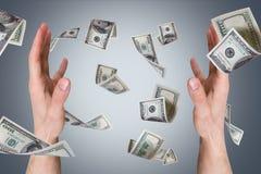 Billets de banque du dollar tombant sur de jeunes mains masculines Image libre de droits