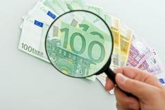 Billets de banque et loupe Photographie stock