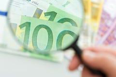 Billets de banque et loupe Photographie stock libre de droits