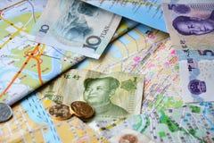 Billets de banque et pièces de monnaie chinois sur cartes chinoises Photographie stock libre de droits