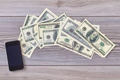 Billets de banque et smartphone du dollar photos stock