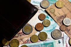 Billets de banque de pièce de monnaie et portefeuille en cuir noir Fond financier photos stock