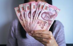 Billets de banque thaïlandais d'argent d'exposition de femme de mains Images libres de droits