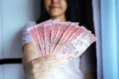 Billets de banque thaïlandais d'argent d'exposition de femme de mains Image libre de droits