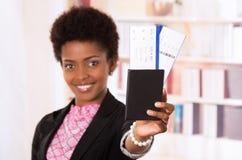 Billets et passeport noirs de femme de bureau Photographie stock libre de droits