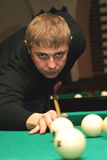 Billiard 1. Cueist lines up a difficult shot. Focus is on the face Royalty Free Stock Images