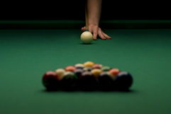 Billiard. Image of billiard balls on the pool table with a person's hand ready to break the balls Stock Photo