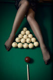 Billiard ball aiming at women legs in stockings Royalty Free Stock Photos