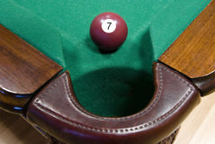 Billiard ball N seven. Cherry red billiard ball with number one in front of corner pocket royalty free stock image