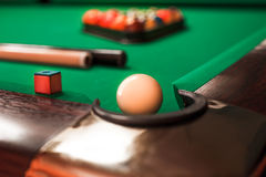 Billiard ball opposite to a pocket. White billiard ball opposite to a pocket. Cue and triangle with balls on the background Stock Photography