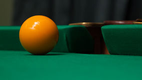 Billiard ball slides in a billiard pocket. Stock Image