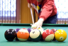 Billiard balls. On green billiard table in foreground and arm with cue in background royalty free stock photography