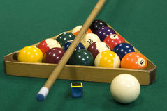 Billiard balls. Coloured billiard balls with numbers in triangular frame, chalk, white ball and cue on green billiard table stock images