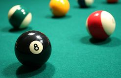 Billiard Balls (American Pool). A close-up shot of an eight ball on a green felt covered pool table with several other billiard balls nicely blurred in the stock photo