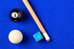 Billiard balls, cue and chalk in a blue pool table. Royalty Free Stock Photography