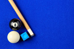 Billiard balls, cue and chalk in a blue pool table. Billiard balls, cue and chalk on a blue pool table. Viewed from above. Horizontal image royalty free stock photo