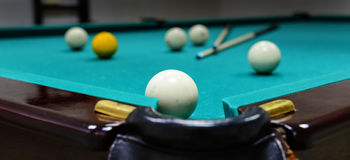 Billiard balls on game table. Billiard balls and two cue sticks on green game table Stock Photos