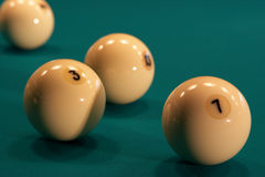 Billiard balls on green baize. White numbered billiard balls on green baize of table Stock Images
