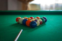 Billiard balls on green table with billiard cue in a hotel hall Stock Photo