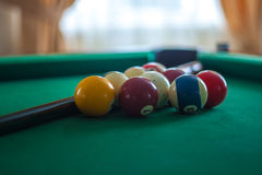Billiard balls on green table with billiard cue in a hotel hall Stock Images