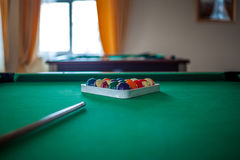 Billiard balls on green table with billiard cue in a hotel hall Royalty Free Stock Photo