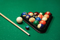 Billiard balls near by cue and chalk. Royalty Free Stock Photography