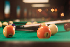 Billiard balls near by cue on the pool table. Stock Image