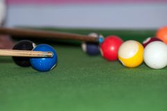 Billiard balls and stick. A player is playing shot on the pool table royalty free stock images