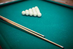 Billiard balls and two Cues in the form of a triangle on the billiard table are ready for the game. Royalty Free Stock Photo