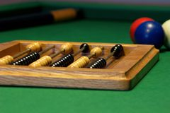 Billiard counter points on a table. Three billiard balls on a billiard table with a cue stick and chalk and a counter points Stock Photography