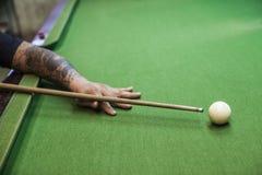 Billiard cue ready to hit white ball. Closeup of man hand with billiard cue ready to hit white ball royalty free stock photo