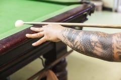 Billiard cue ready to hit white ball. Closeup of man hand with billiard cue ready to hit white ball royalty free stock image