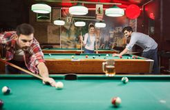 Billiard games - happy friends enjoying playing pool together. Billiard games -Happy young friends enjoying playing pool together royalty free stock photo
