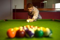 Starting billiard match. The billiard player is starting to play billiard game or snooker with first shooting on billiard table in billiard club stock photos
