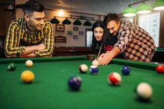 Billiard players with cues, friends in poolroom. Billiard players with cues at the table with colorful balls, friends in poolroom. Group plays american pool game royalty free stock image