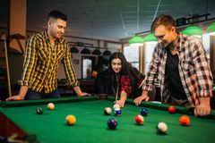 Billiard players with cues at the table with balls. Billiard players with cues at the table with colorful balls, poolroom. Group plays american pool game in stock photography